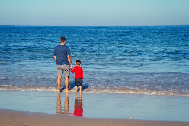 Vader die met zon in strand loopt