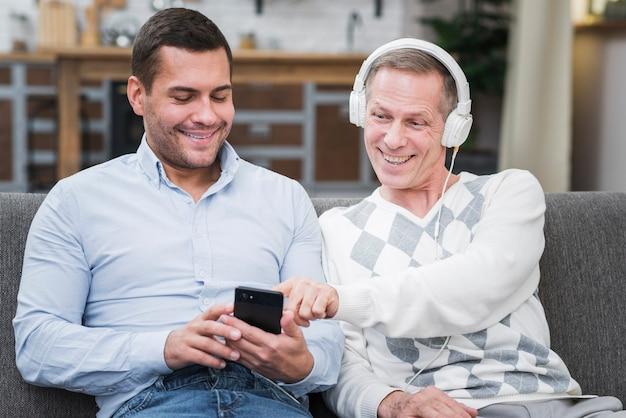 Vader die muziek kiest uit de telefoon van zijn zoon