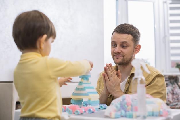 Vader die op zijn zoonsspeelgoed wordt geconcentreerd