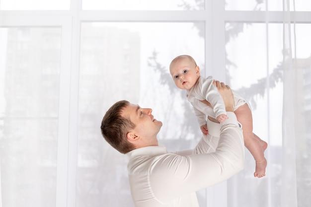 Vader die pasgeboren baby thuis bij het raam houdt