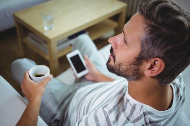 Vader die telefoon met behulp van terwijl het hebben van koffie in woonkamer