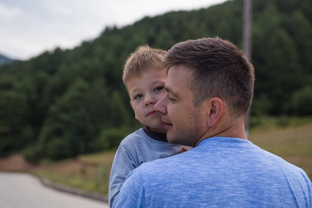 Vader die weinig zoon in de lucht steunt die samen de papa en het kind spelen die van de familielevensstijl openlucht de dagvakantie van het ouderschapconcept lopen