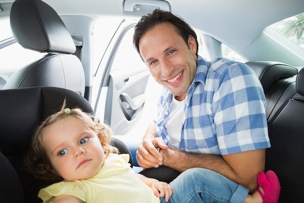 Vader die zijn baby in de autozetel beveiligt
