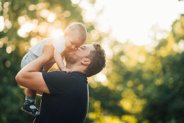 Vader die zijn baby in het park kust
