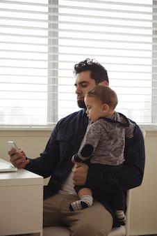 Vader die zijn baby vasthoudt tijdens het gebruik van de mobiele telefoon aan het bureau