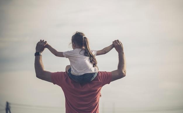 Vader die zijn dochter op de schouders houdt