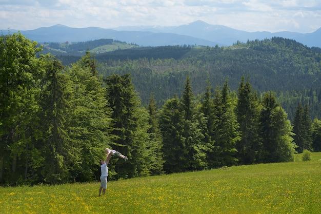 Vader die zijn jonge zoon omcirkelt. bos en bergen
