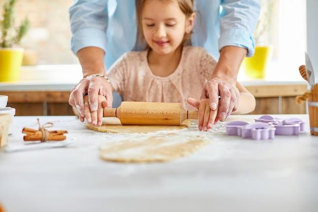 Vader die zijn kleine dochter toont hoe te om deeg voor koekjes te rollen