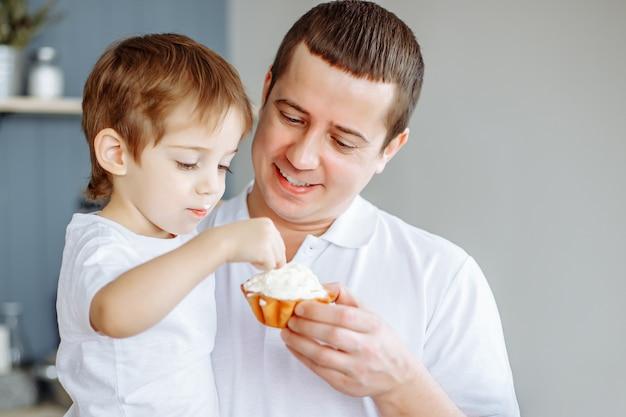 Vader die zijn kleine zoon in keuken voedt.