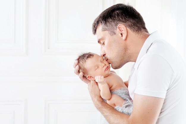 Vader die zijn pasgeboren baby in handen houdt.