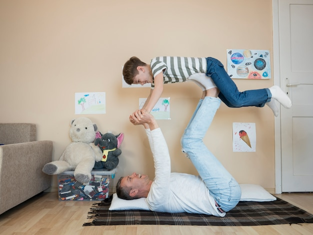 Vader die zijn zoon in de lucht houdt
