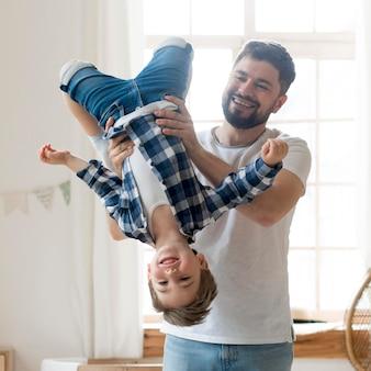 Vader die zijn zoon ondersteboven houdt
