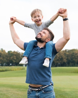 Vader die zijn zoon op zijn schouders vooraanzicht houdt