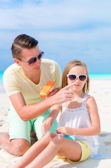 Vader die zonroom toepast op dochterneus. portret van schattig meisje in zonnebrandcrème