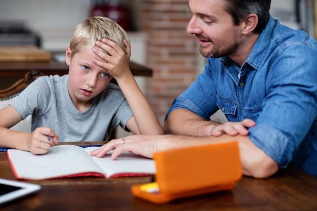Vader die zoon helpt met zijn huiswerk in keuken