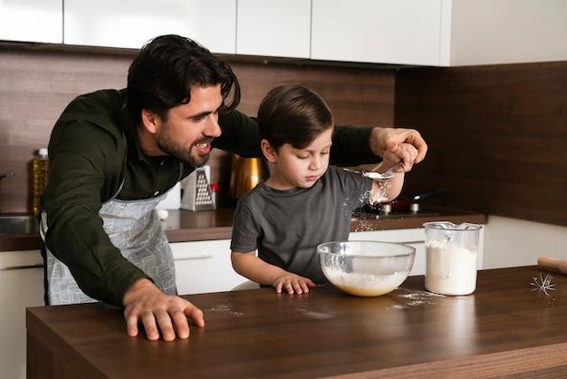 Vader die zoon helpt om deeg te maken