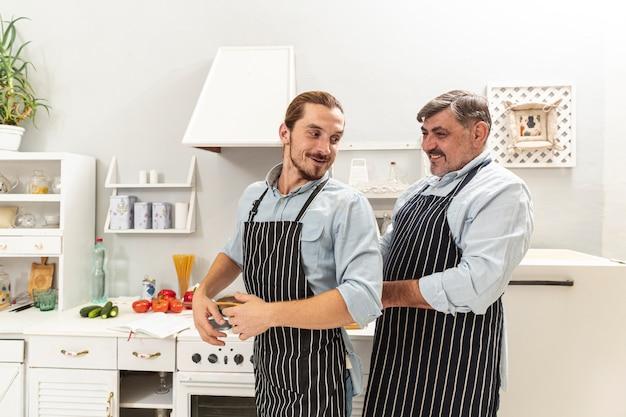 Vader die zoon met keukenschort helpt