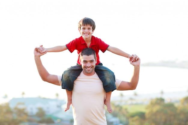 Vader die zoon op de rug rit geeft