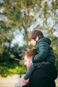 Vader die zoon op schouders vervoert