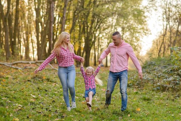 Vader, dochter en moeder buiten lopen. gelukkig gezin.
