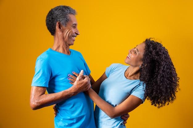 Vader en afro dochter lachend op gele achtergrond. vaderdag concept