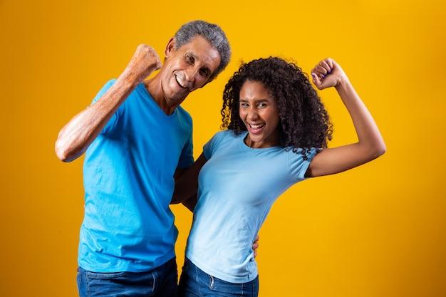 Vader en afro-dochter op gele achtergrond die armen opheft om het bereiken van het doel te vieren. vader en dochter juichen de overwinning toe