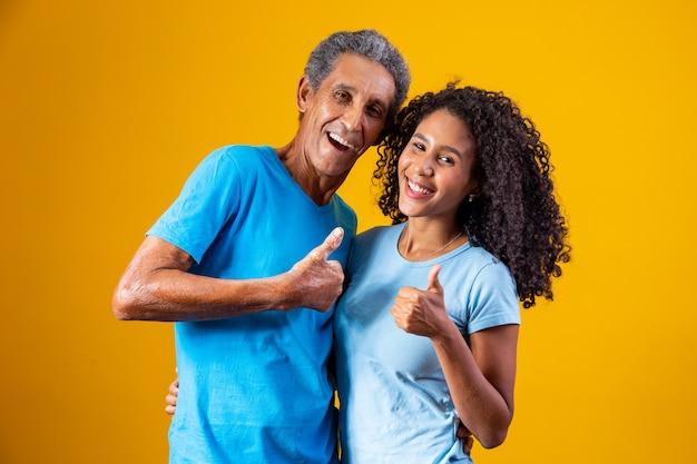 Vader en afro dochter op gele achtergrond met duim omhoog maken ok, positief teken.
