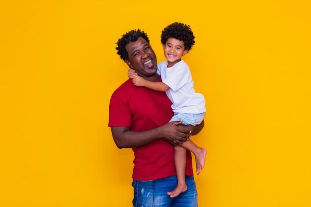 Vader en afro zoon op gele achtergrond glimlachen. vaderdagconcept