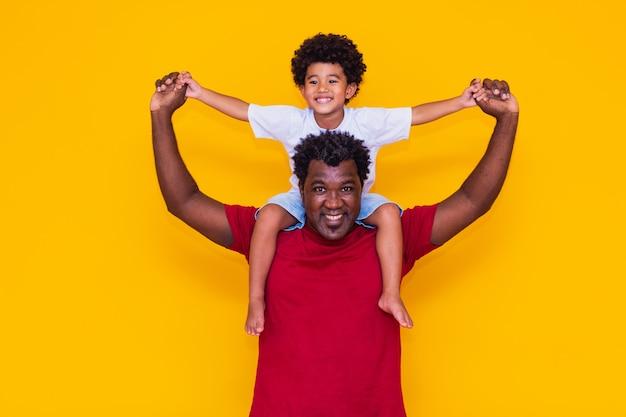 Vader en afro zoon op gele achtergrond glimlachend en spelen. vaderdagconcept