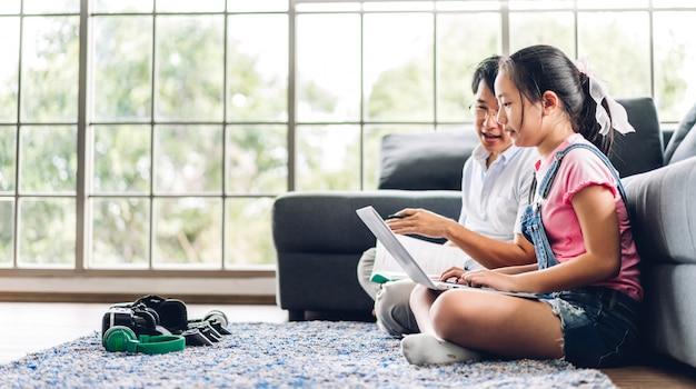 Vader en aziatisch jong geitjemeisje die en laptop computer leren bekijken die huiswerk maken die kennis bestuderen met online onderwijs e-leersysteem. kinderen videoconferentie met leraarstutor thuis