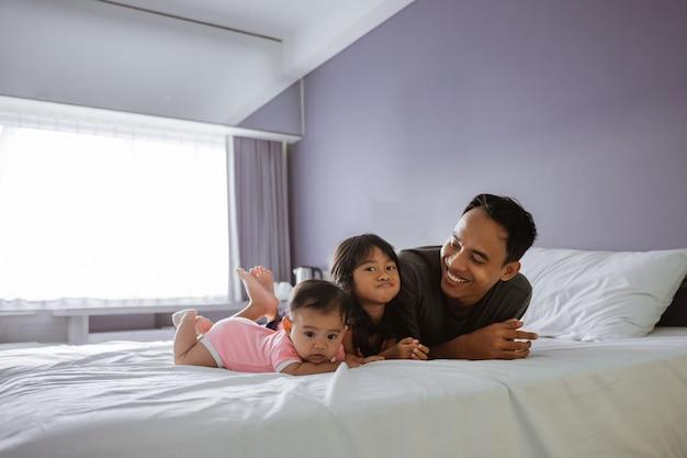 Vader en de twee kinderen liggen op het bed