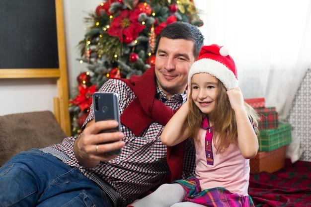 Vader en dochter bij de kerstboom met een smartphone een selfie maken, communiceren via videoverbinding. kerstgroeten, een geschenkdoos, een meisje met een kerstmuts die hallo zwaait.
