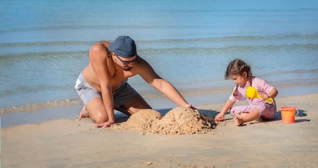 Vader en dochter bouwen het zandkasteel op het strand. man speelt met zijn dochter aan zee