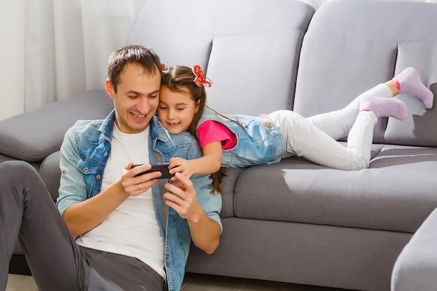Vader en dochter delen iets grappig in een mobiele telefoon
