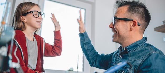 Vader en dochter die aan elektronische componenten en het toejuichen werken