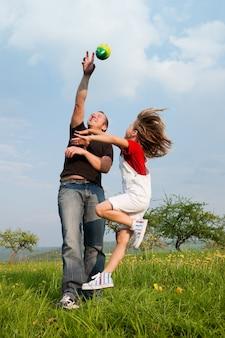 Vader en dochter die de bal vangen