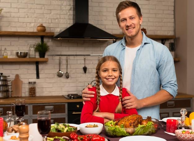 Vader en dochter die de camera in de keuken bekijken