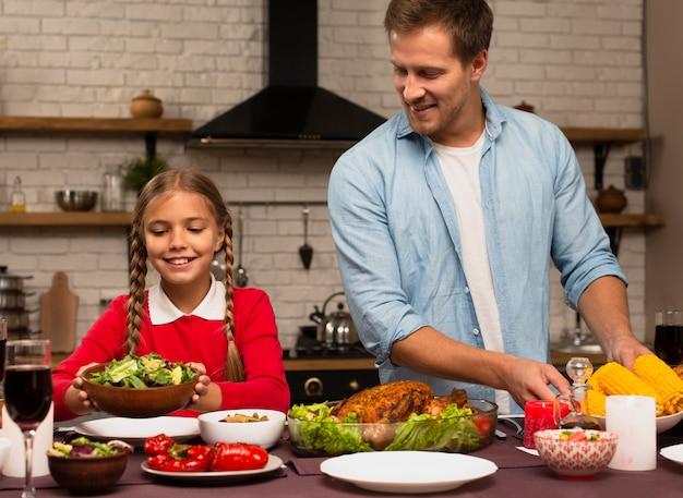 Vader en dochter die de maaltijd voorbereiden