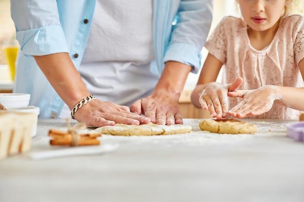 Vader en dochter die deeg samen in keuken voorbereiden