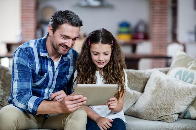 Vader en dochter die digitale tablet in woonkamer gebruiken