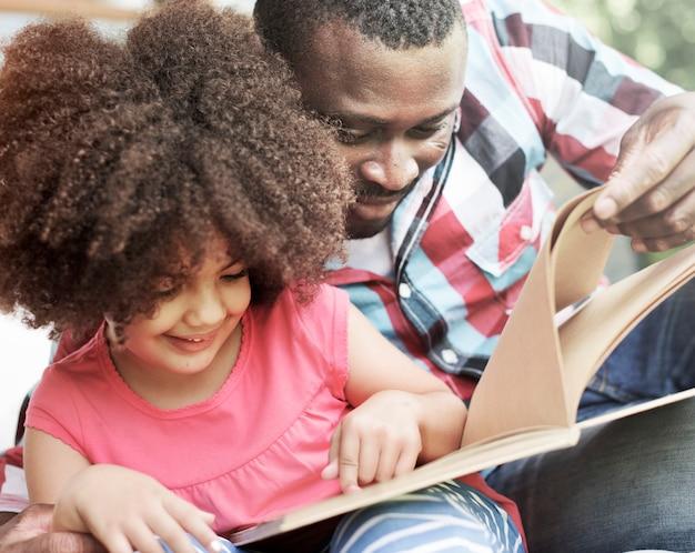 Vader en dochter die een boek samen lezen