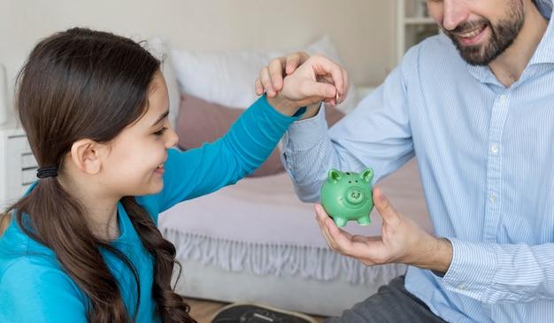 Vader en dochter die geld in spaarvarken zetten
