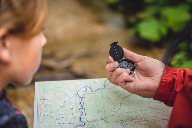 Vader en dochter die in bos wandelen en kaart controleren