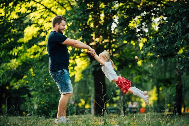 Vader en dochter die in cirkel spinnen