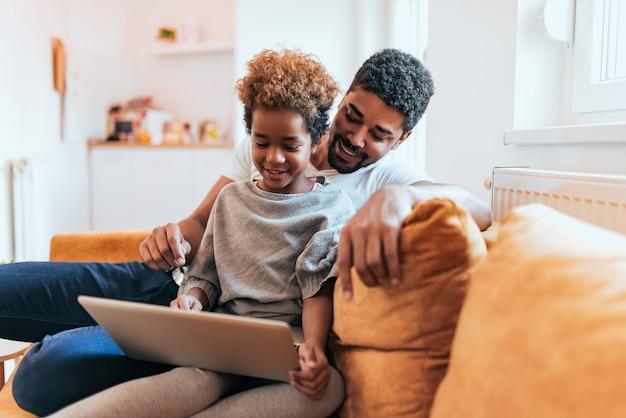 Vader en dochter die laptop samen thuis gebruiken.