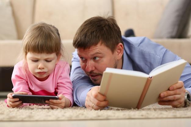 Vader en dochter die op vloer thuis liggen