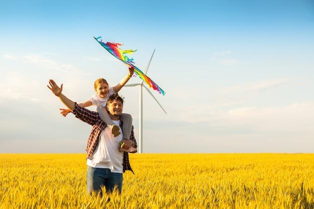 Vader en dochter die pret hebben, die met vlieger samen spelen
