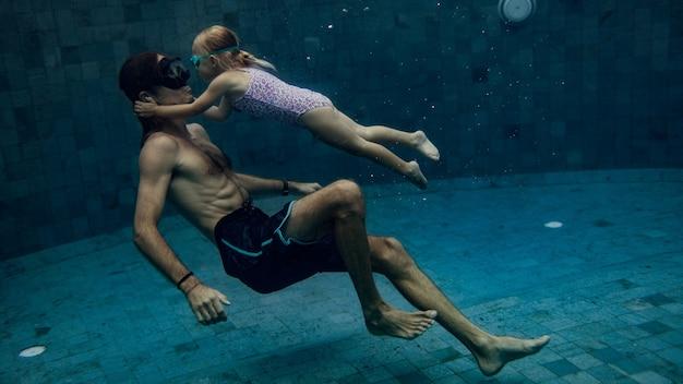 Vader en dochter die samen in pool zwemmen