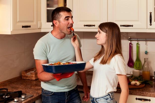 Vader en dochter die voedsel in de keuken voorbereiden