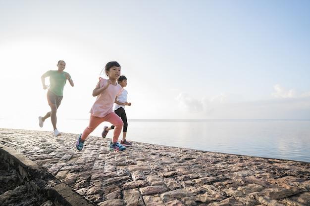 Vader en dochter doen oefeningen om buiten tegen elkaar te racen